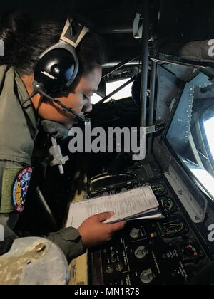U.S. Air Force Senior Airman Avemaoe Liaiga, 351st Air Refueling Squadron KC-135 boom operator, RAF Mildenhall, England, reviews a post-air refueling checklist after refueling U.S. Navy aircraft from the USS George H.W. Bush (CVN 77) and British Royal Air Force Eurofighter Typhoons over the Atlantic Ocean during exercise Saxon Warrior, Aug. 8, 2017. Saxon Warrior is a United States and United Kingdom co-hosted carrier strike group exercise that demonstrates interoperability and capability to respond to crises and deter potential threats. (U.S. Air Force photo by 2nd Lt. Nathanael Callon) - Stock Photo