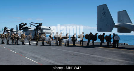 """170811-N-DC385-219 CORAL SEA (Aug. 11, 2017) Marines, assigned to the 31st Marine Expeditionary Unit (MEU), embark an MV-22B Osprey, assigned to the """"Dragons"""" of Marine Medium Tiltrotor Squadron (VMM) 265 (Reinforced), on the flight deck of the amphibious assault ship USS Bonhomme Richard (LHD 6) as part of an embassy reinforcement simulation during a certification exercise (CERTEX). Bonhomme Richard, flagship of the Bonhomme Richard Expeditionary Strike Group, is supporting a CERTEX that will evaluate the 31st MEU on crisis response operations for a number of potential contingencies. CERTEX,  - Stock Photo"""