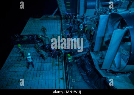 170811-N-DL434-182 CORAL SEA (Aug. 11, 2017) Marines, assigned to the 31st Marine Expeditionary Unit (MEU), depart the well deck of the amphibious assault ship USS Bonhomme Richard (LHD 6) in a combat rubber raiding craft (CRRC). Bonhomme Richard, flagship of the Bonhomme Richard Expeditionary Strike Group (ESG), is operating in the Indo-Asia-Pacific region to enhance partnerships and be a ready-response force for any type of contingency. (U.S. Navy photo by Mass Communication Specialist Seaman Apprentice Gavin Shields/ Released) - Stock Photo