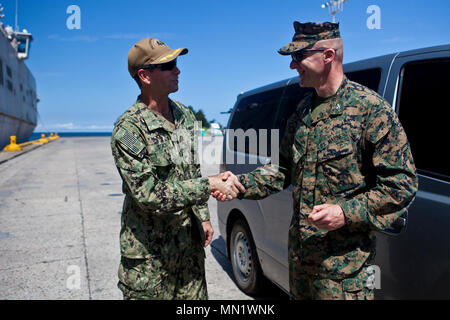U.S. Marine Col. Michael V. Samarov, the commanding officer of Special Purpose Marine Air-Ground Task Force - Southern Command, shakes hands with and awards a challenge coin to U.S. Navy Capt. Steven P. Stacy,  the Southern Partnership Station-Expeditionary Fast Transport 17 mission commanding officer for the USNS Spearhead (T-EPF-1) in Puerto Castilla, Honduras, Aug. 8, 2017. The Marines and sailors of SPMAGTF-SC are deployed to Central America to conduct security cooperation training and engineering projects with their counterparts in several Central American and Caribbean nations. (U.S. Mar - Stock Photo