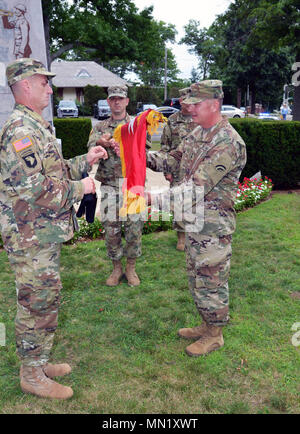 Major General Steven Ferrari ( right) unfurls his general officers flag with the assistance of 42nd Infantry Division Command Sgt. Major Justin Lenz following his promotion during a ceremony marking the Rainbow Division's centennial on Saturday, August 12, 2017 at Garden City, N.Y. The ceremony marked the division's concentration at Camp Albert Mills here in August and September 1017. New York State Division of Military and Naval Affairs photo by New York Guard Capt. Mark Getman. - Stock Photo