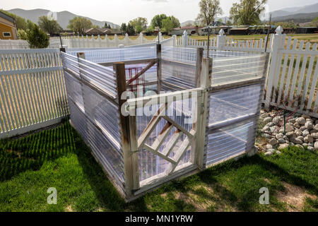 Residential vegetable garden with fiberglass panel walls to deflect wind - Stock Photo