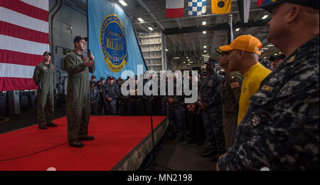 170814-N-NQ487-106  NORFOLK (Aug. 14, 2017) Capt. Nicholas J. Dienna, commanding officer of the aircraft carrier USS Harry S. Truman (CVN 75), addresses Sailors during an all-hands call in the hangar bay. This was the first all-hands call held by Dienna since assuming command July 28. (U.S. Navy photo by Mass Communication Specialist Seaman Kaysee Lohmann/Released) - Stock Photo