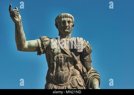 Rome, Bronze statue of emperor Caesar Nervae Trajan, Forum of Caesar Nervae Trajan in the background - Stock Photo