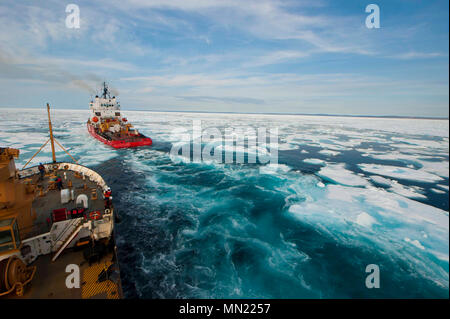 The crew of U.S. Coast Guard Cutter Maple follows the crew of Canadian Coast Guard Icebreaker Terry Fox through the icy waters of Franklin Strait, in Nunavut, Canada, August 12, 2017. The Canadian Coast Guard assisted Maple's crew by breaking and helping navigate through ice during several days of Maple's 2017 Northwest Passage transit. U.S. Coast Guard photo by Petty Officer 2nd Class Nate Littlejohn. - Stock Photo