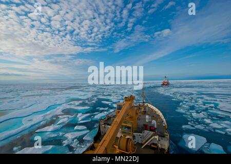 The crew of U.S. Coast Guard Cutter Maple follows the crew of Canadian Coast Guard Icebreaker Terry Fox through the icy waters of Franklin Strait, in Nunavut Canada, August 11, 2017. The Canadian Coast Guard assisted Maple's crew by breaking and helping navigate through ice during several days of Maple's 2017 Northwest Passage transit. U.S. Coast Guard photo by Petty Officer 2nd Class Nate Littlejohn. - Stock Photo