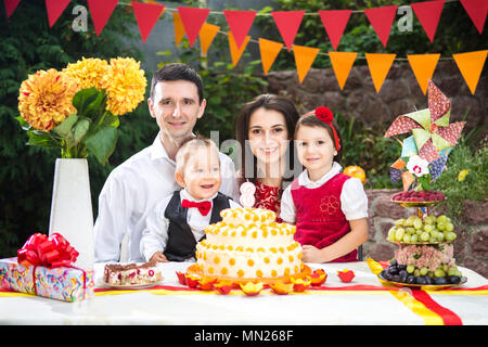 family of four people father mom son and daughter celebrates daughter's birthday three years sitting at a festive decorated table decor and a big deli - Stock Photo