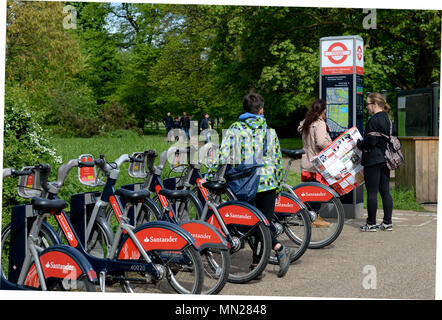 Tourists choose a bike to hire at a docking station in central London , Kensington park - Stock Photo