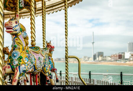A view from Brighton Pier featuring the traditional horse carousel on the pier and the British Airways i360 observation tower in the distance. - Stock Photo