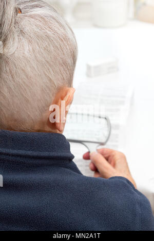 Old woman sitting at a table in her living room using a magnifying glass to read the information sheet of her prescribed medicine - Stock Photo
