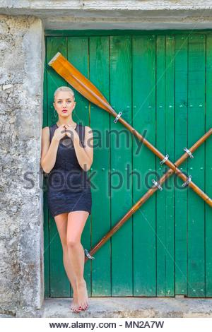 Young woman standing barefeet wearing small little Black dress minidress clothing - Stock Photo
