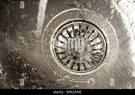 Sink drain in the kitchen with running water - Stock Photo