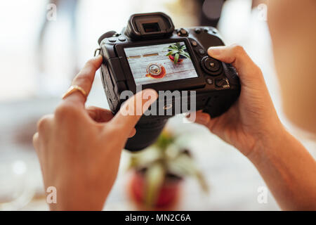 Close up of a blogger taking photos of a glass teapot and a plant using a professional camera for her food blog. Food blogger shooting photos for her  - Stock Photo