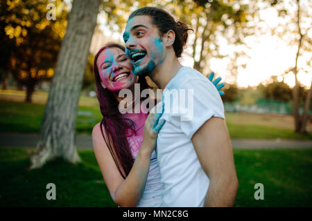 Smiling young couple with colored powder smeared on their faces. Cheerful man and woman enjoying festival of colors outdoors at park. - Stock Photo