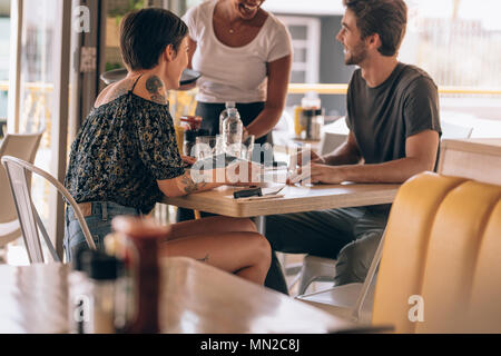 Young couple sitting at cafe giving order to a female waiter. Man placing order to a waitress at restaurant while sitting with his girlfriend. - Stock Photo