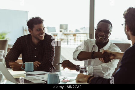 Businessmen discussing work sitting at conference table in office. Men shaking hands and smiling during a business meeting. - Stock Photo