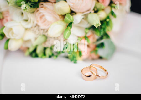 Wedding rings lie on white surface against background of bouquet of flowers - Stock Photo
