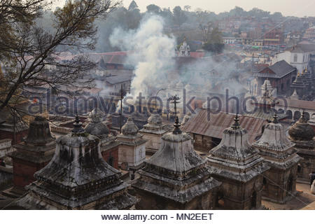 Many chaityas stand amongst other buildings in the Hindu temple complex at Pashupatinath. In the background smoke rises from the cremation ghats as a  - Stock Photo