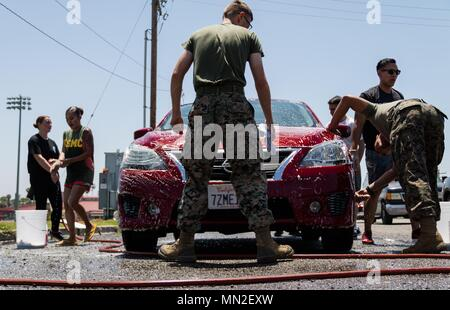 U.S. Marines with Combat Logistics Battalion 1, Combat Logistics Regiment 1, 1st Marine Logistics Group, work to detail a car during a fundraising car wash on Marine Corps Base Camp Pendleton, Calif. May 10, 2018, May 11, 2018. Funds from the car wash will be allocated towards the unit's Marine Corps ball, held annually on or around November 10 to celebrate the Marine Corps' birthday. (Marine Corps photo by Cpl. Desiree King). () - Stock Photo