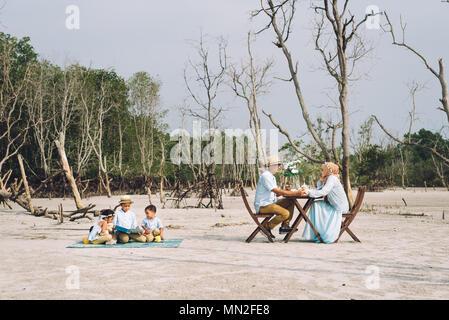 Asian happy family having a picnic. love and happy family concept - Stock Photo