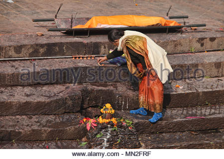 A woman lights incense by a body to be cremated at the steps leading to the bank of the Bagmati River at the Pashupatinath cremation ghats in Nepal. A - Stock Photo