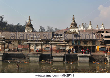 Cremation ghats along the bank of the Bagmati River at Pashupatinath in Nepal. The Bagmati runs into the Ganges further South and is considered equall - Stock Photo