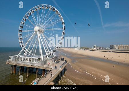 Ferris wheel at Scheveningen pier and beach, with 2 people on zip wire in background, Wassenaar district, The Hague (Den Haag), Netherlands - Stock Photo