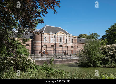 Horse riders outside the Royal Stables building (Koninklijke Stallen), viewed from Palace Garden (Paleistuin), The Hague, Netherlands. - Stock Photo