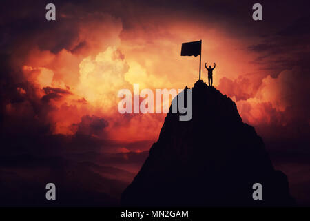 Self overcome concept as a businessman lift his hands up on the top of al mountain reaching the finish flag. Road to win and success over sunset backg - Stock Photo