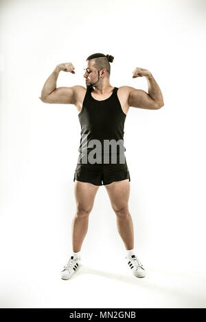 portrait - the trainer on bodybuilding shows an exercise to warm - Stock Photo