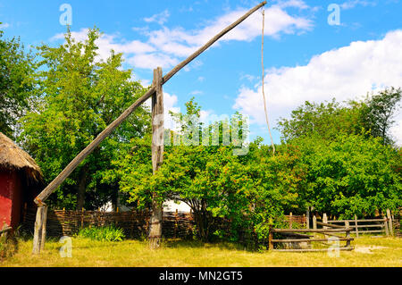 picturesque rural landscape with a well a crane - Stock Photo