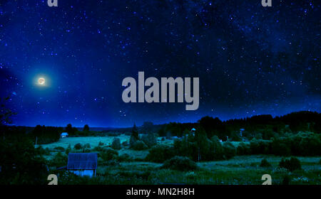 Summer rural night landscape with a bright flickering starry sky and the full moon over the sleeping blossoming valley and village - Stock Photo