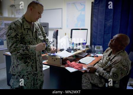 U.S. Navy Petty Officer 1st Class Francisco Valentin, fuels management specialist with the Combined Joint Task Force-Horn of Africa Logistics Directorate's Base Operating Support-Integrator office, provides updates on support resources to Lt. Col. Derek Hart, director of BOS-I, at Camp Lemonnier, Djibouti, August 18, 2017.  Hart is responsible for overseeing the continuous flow and coordination of mission-essential resources to forward-deployed U.S. service members throughout Somalia. U.S. Africa Command designated CJTF-HOA as BOS-I in August 2016, putting the 500-person task force in charge o - Stock Photo