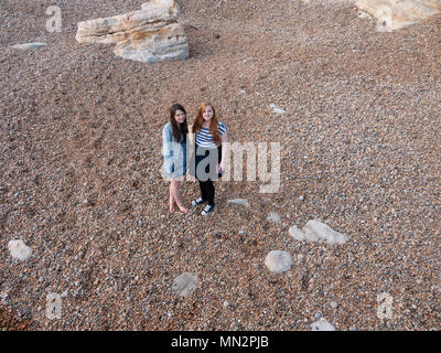 Two young ladies on a pebble beach - Stock Photo