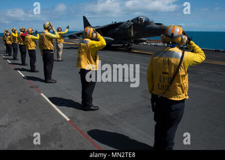 """170822-N-RU971-294 CORAL SEA (August 22, 2017) Air department Sailors salute the pilot of an AV-8B Harrier, assigned to the """"Tomcats"""" of Marine Attack Squadron (VMA) 311, before it takes off from the flight deck of the amphibious assault ship USS Bonhomme Richard (LHD 6). VMA-311 concludes its """"farewell tour"""" with the Bonhomme Richard Expeditionary Strike Group (BHR ESG) and the 31st Marine Expeditionary Strike Group (MEU) as the ESG transitions to F-35B Lightning II Joint Strike Fighters in the winter of 2017. Bonhomme Richard, flagship of the BHR ESG, is operating in the Indo-Asia Pacific re - Stock Photo"""