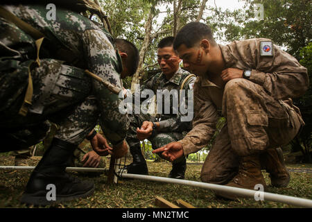 CAIRNS, Australia – U.S. Marine Cpl. Nicolas Villanueva, right, motor transportation operator, Combat Logistics Detachment, Marine Rotational Force Darwin, works with soldiers from the Chinese People's Liberation Army to build a hut during Indigenous Australian culture classes for Exercise Kowari 2017 Aug. 23, 2017. After the opening ceremony, the Soldiers and Marines also took part in some traditional activities such as boomerang throwing and tribal face painting to introduce those visiting from the US and China to Indigenous Australian culture. Kowari is an annual training activity held in A - Stock Photo