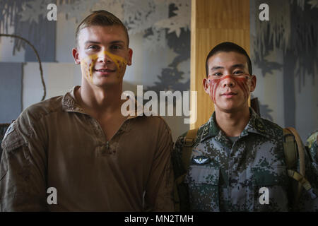 CAIRNS, Australia – U.S. Marine Cpl. Micheal Smith, left, rifleman, Company K, 3rd Battalion, 4th Marine Regiment, Marine Rotational Force Darwin, poses for a photo with a soldier from the Chinese People's Liberation Army after having their faces painted in Aboriginal designs during Indigenous Australian culture classes for Exercise Kowari 2017 Aug. 23, 2017. The Soldiers and Marines also took part in some traditional activities such as boomerang throwing and hut building to introduce those visiting from the US and China to Indigenous Australian culture. Kowari is an annual training activity h - Stock Photo