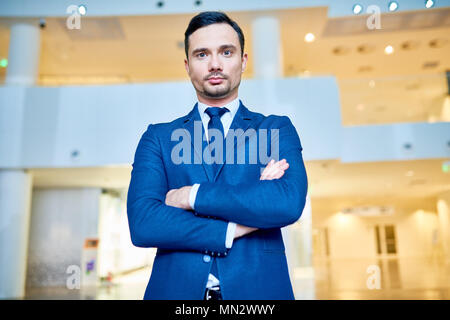 Waist up portrait of successful young businessman wearing blue suit posing confidently and looking at camera while standing with arms crossed in moder - Stock Photo