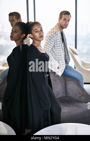 Beautiful interracial couple is posing on the large windows background in the flat. Black girls in dark clothes leans on the mirrored wall, white guy  - Stock Photo