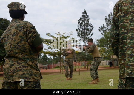 U.S. Marines assigned to Special Purpose Marine Air-Ground Task Force-Crisis Response-Africa logistics combat element demonstrate the standing firing position to Uganda People's Defence Force soldiers at Camp Singo, Uganda, Aug. 28, 2017. SPMAGTF-CR-AF LCE is deployed to conduct limited crisis-response and theater-security operations in Europe and Africa. (U.S. Marine Corps Photo by Staff Sgt. Rebekka S. Heite/Released) - Stock Photo