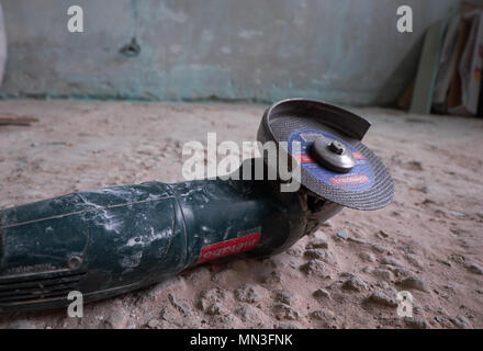 Side grinder on a floor in front of a dirty wall. Overhaul concept - Stock Photo