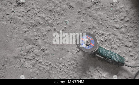 Angle grinder on a old dirty concrete floor. Overhaul concept - Stock Photo