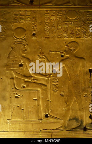 Egypt. Abydos. Temple of Seti I. New Kingdom. 19th Dynasty. Relief with original polychrome. The Pharaoh making offerings to goddess Isis. 1292-1189 BC. - Stock Photo