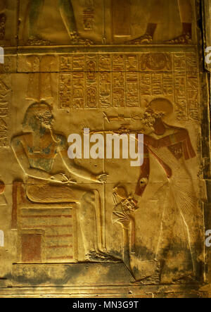 Egypt. Abydos. Temple of Seti I. New Kingdom. 19th Dynasty. Relief with original polychrome. The Pharaoh making offering of incense before a god. 1292-1189 BC - Stock Photo