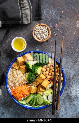 Buddha Bowl with quinoa, tofu, broccoli, sweet potato and cucumber. Nourishing buddha bowl. Healthy vegan or vegetarian salad bowl, table top view - Stock Photo