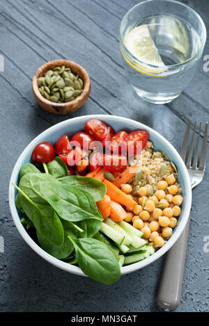 Chickpea salad bowl on concrete background. Healthy buddha bowl with baby spinach, baby carrots, chickpeas, quinoa and tomatoes - Stock Photo