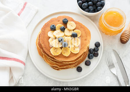 Homemade pancakes with blueberries and banana on white plate. Stack of corn pancakes. Pancakes with fruits and honey on a table - Stock Photo