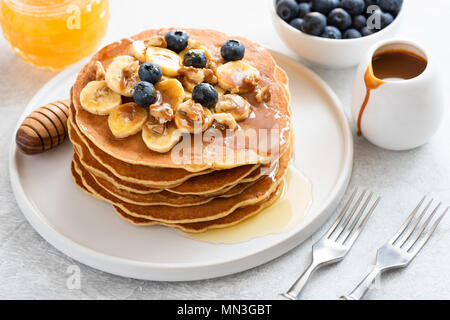 Stack of pancakes with banana, blueberries, walnuts, honey and caramel sauce on white plate. Closeup view. Breakfast pancakes with maple syrup - Stock Photo