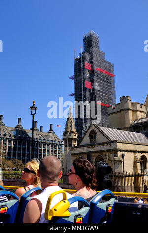 London Sightseeing bus passing the houses of Parliament and Big Ben covered in Scaffolding - Stock Photo