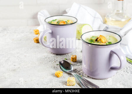 Two portions of homemade zucchini creamy soup with bread crumbs in mugs on a light concrete background. - Stock Photo